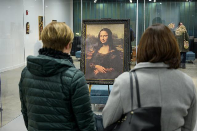 Women admire the reproduction of the Mona Lisa at the da Vinci exhibit at Kean