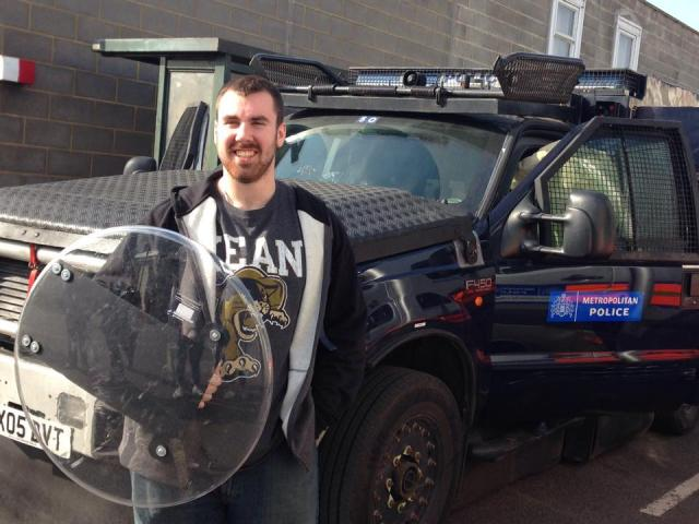 A Kean criminal justice student holds a shield near a Metropolitan Police vehicle.