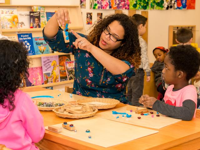 Kean student interacts with 2 children at Kean's Child Care Center