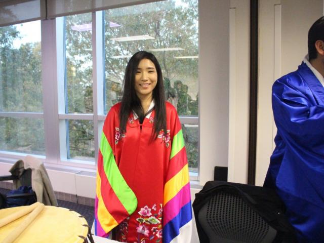 Student standing in colorful clothing smiling at camera