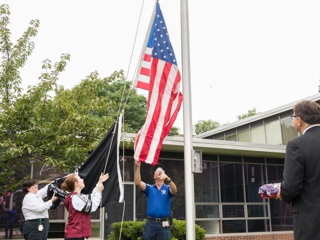 An American flag that flew over Ground Zero is raised at Kean University.