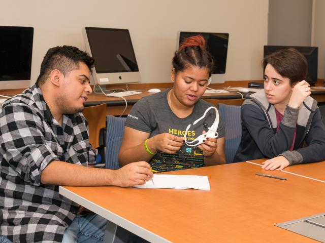 Kean students examine the BCI headgear being used in their research.