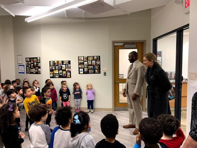 Pittman and Wolfe speak to a hallway full of children from the Child Care Center.