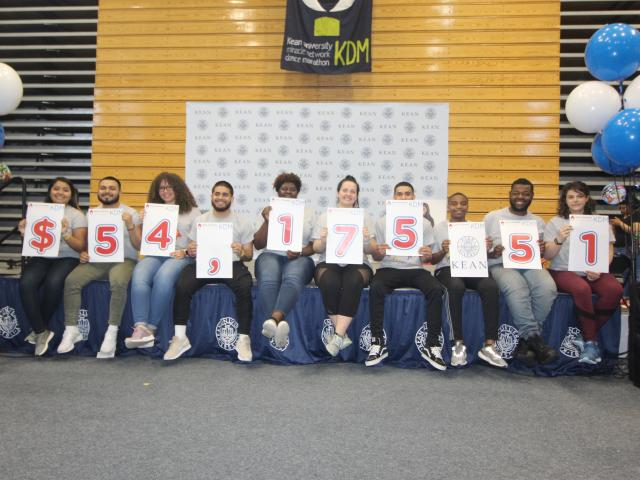 Kean University students proudly display the fundraising tally for the Kean Dance Marathon.