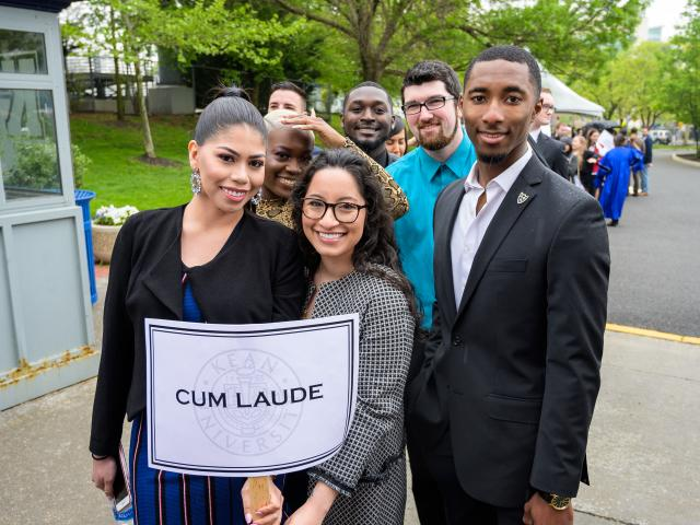 Cum Laude students pose behind their sign saying they are cum laude