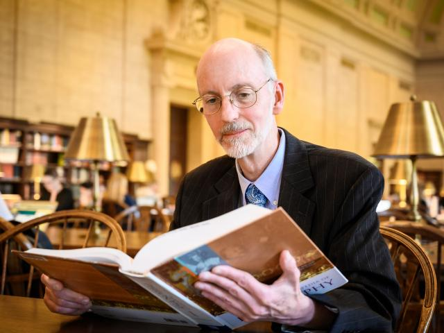 Dr. Jeff Toney sits reading a book at the MIT library