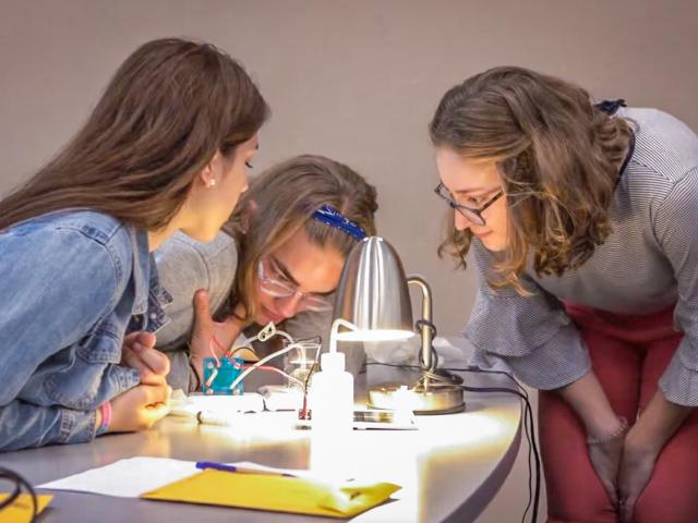 Three students collaborate on a renewable energy experiment.