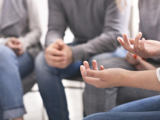 A photo of the people's hands, as they sit in a group talking