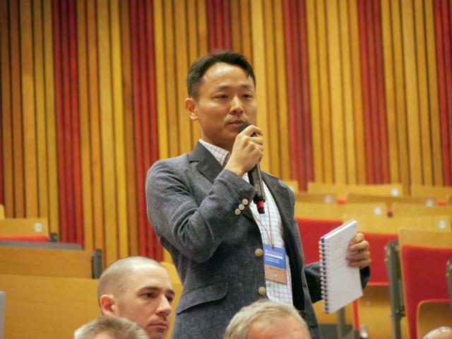 Kean University assistant professor Bok Jeong holding a microphone and speaking at an event.