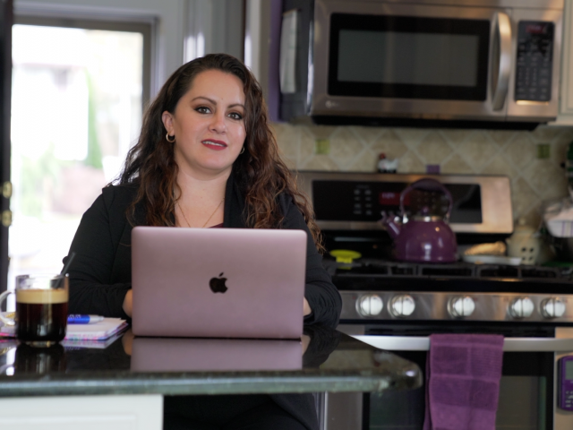 A Kean Online student with a laptop in her kitchen.