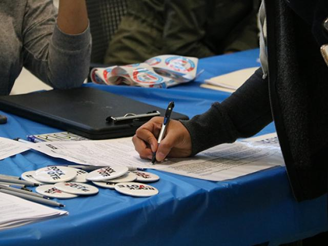 A closeup of a student registering to vote at a desk.