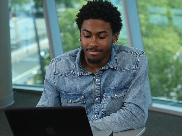 A Kean University student works on a laptop.