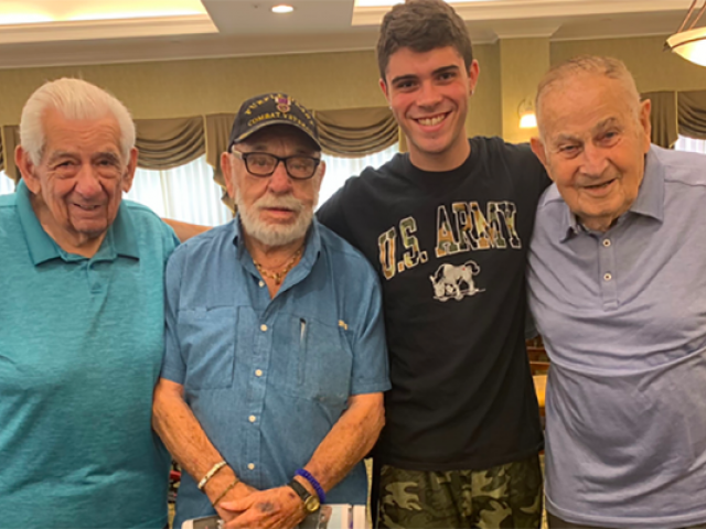 Kean student, Michael Naya, smiles for a photo with 3 World War 2 veterans.