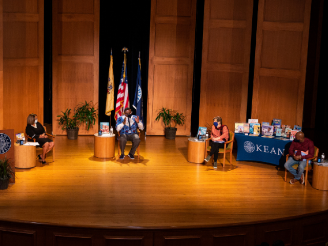 Sancha Gray, Dr. Repollet, Randi Weingarten and Ras Baraka, wearing face masks, sit on stage at Enlow Recital Hall.
