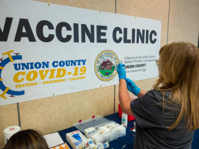 A nurse prepares a COVID-19 vaccine at the vaccination site on Kean University's campus.