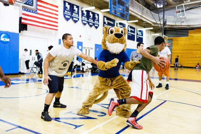 Kean University Cougar playing basketball with students