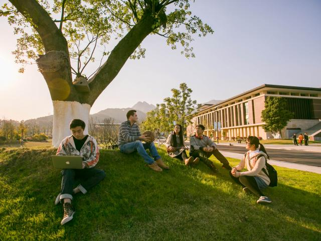 Wenzhou-Kean University students talking on the grass.