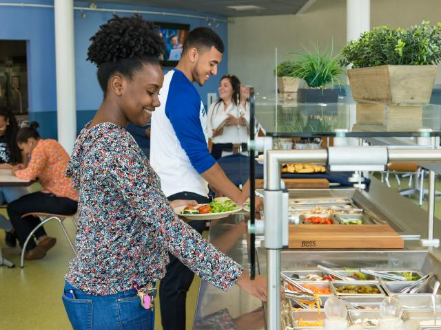 Kean University students serve themselves at the residence hall cafeteria salad bar