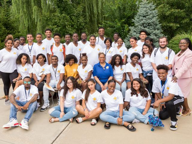 Outdoor group photo of EEO students and the program's director