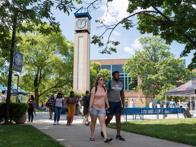 Students walk on Kean's campus in Union, with the clock tower behind them.