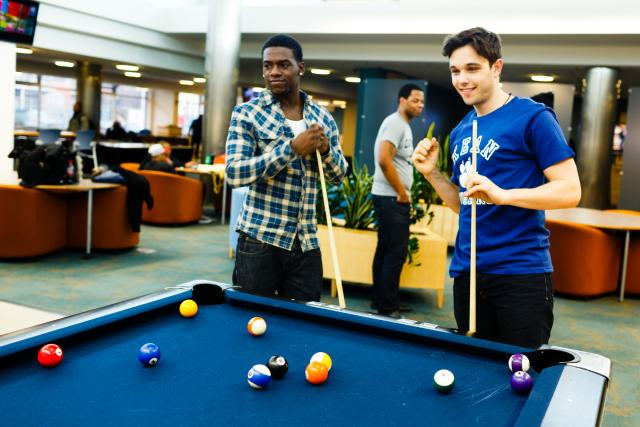 Two students shooting pool