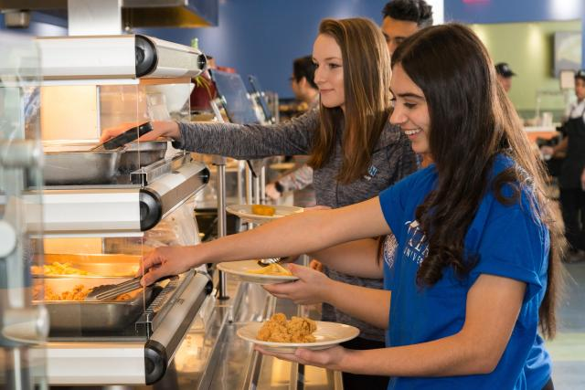 Students serve themselves in the cafeteria line