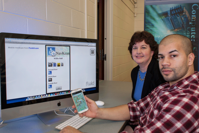 Pat Morreale, Ph.D. with student JimenezL holding a cell phone, sitting in front of a wide angle computer screen