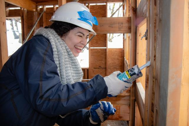 Female student holds caulking gun and caulks a house being built