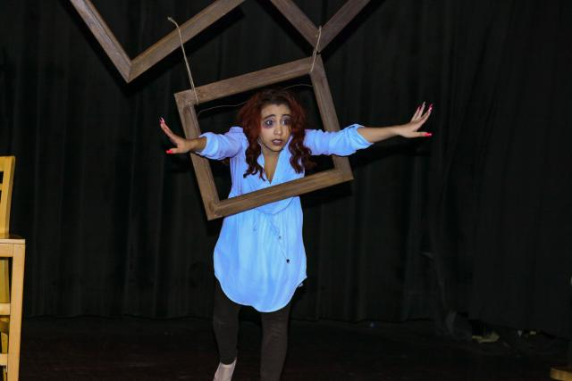An actress on stage poses through a hanging, open window.