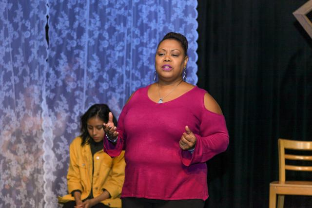 Woman on stage in bright, purple shirt acting out monologues of a victim of domestic violence.