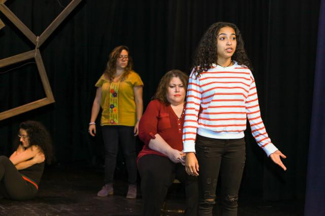 Three actresses stand on stage acting the monologues of those affected by domestic violence.
