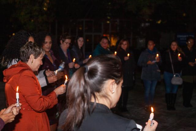 Kean students, actresses, the YWCA and others gather around with lit candles for a candlelight vigil outside of clock tower at Kean University