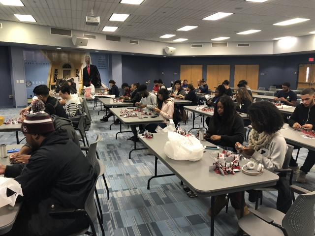 A whole room of students put together Salvation Army bells