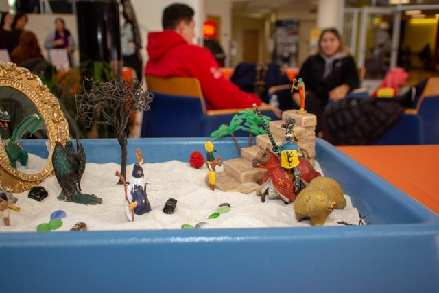 Children's sand art is displayed on a table to show what children's involved in domestic violence situations may do in therapy to express themselves.