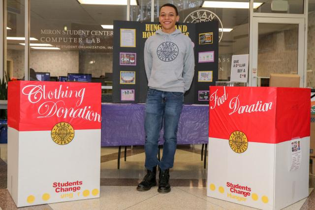 Roberto Adams poses in front of poster about homelessness with clothing and food drive boxes next to him