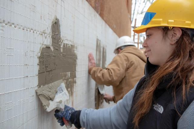 A student uses tools to stucco the side of a home.