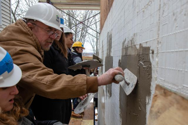 The site manager, Bob at Habitat for Humanity uses tools to show students how to stucco the side of the house.