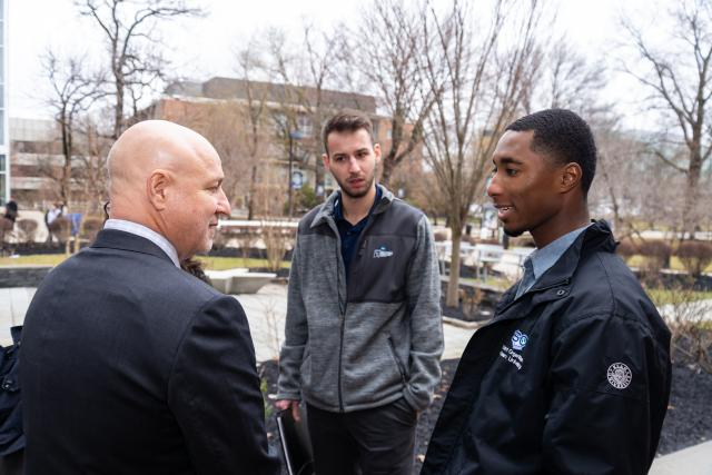 Chef Tom Colicchio talks with two Kean University students on the Union campus.