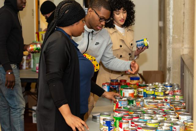 Three students organize canned goods on a table to see all of the donations for the food pantry laid out.