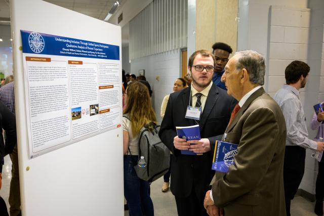 A student shows Dr. Farahi his research work.