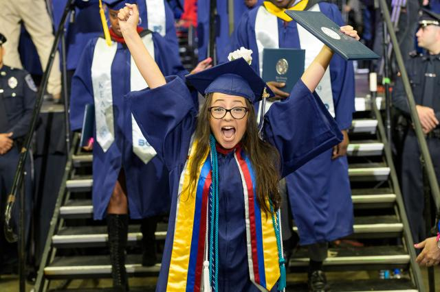 A Kean University student cheers after receiving her diploma at commencement.