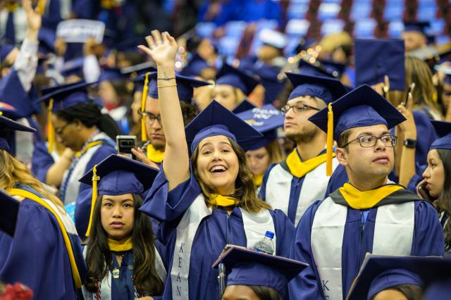 A student waves to family and friends at Kean University's Undergraduate Commencement