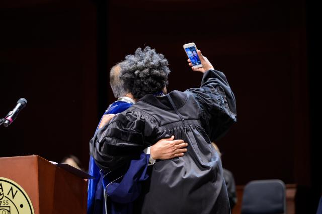 Commencement Speaker Nancy Giles takes a selfie on stage with Kean President Dawood Farahi.
