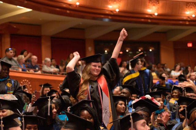 A student in Nathan Weiss Graduate College cheers at Commencement.