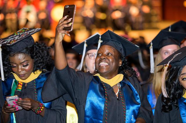 A student takes a selfie at her seat at Nathan Weiss Graduate College Commencement.