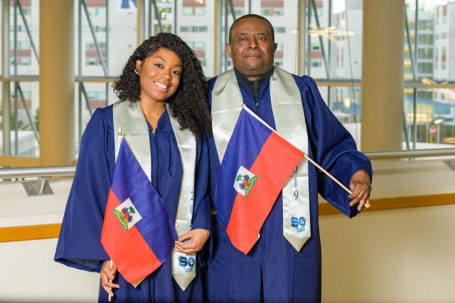Daughter and father graduates, Welena (L) and Wisner Noel, proudly display the Haitian flag. The family has proud Haitian roots.