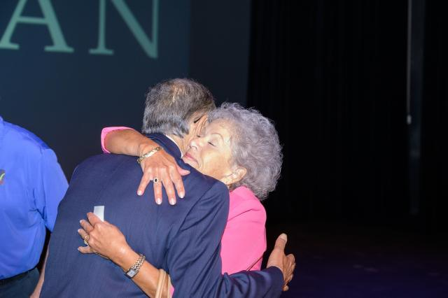 Kean University Board of Trustees Chair Ada Morell hugs President Dawood Farahi after he announced his fai