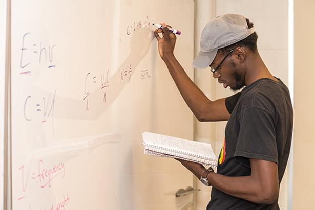 A Kean student works at a whiteboard.
