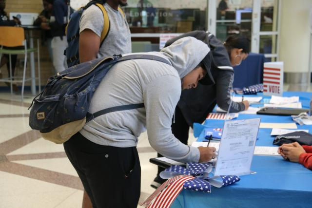 Student with backpack signing voter registration form