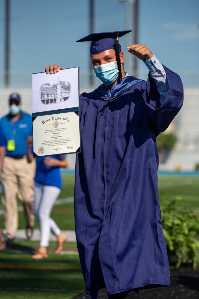 Grad proudly displays diploma and pumps fist
